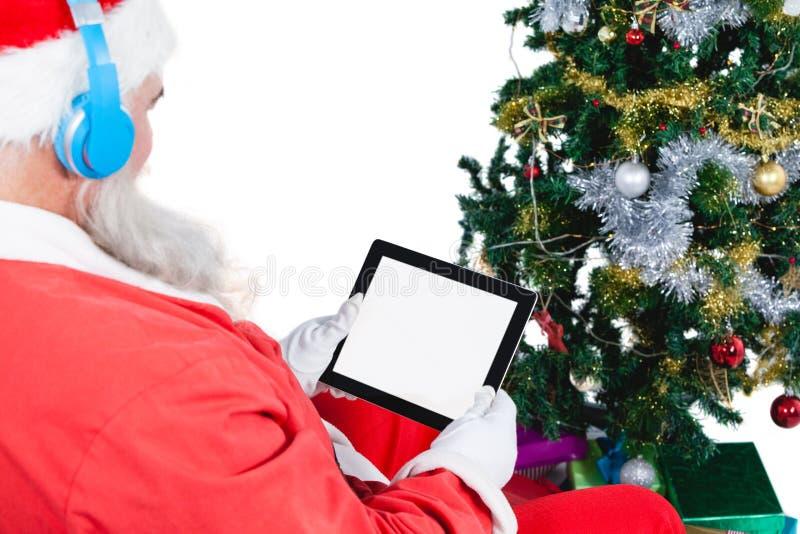 Papai Noel que usa a tabuleta digital com árvore e presentes de Natal imagem de stock royalty free