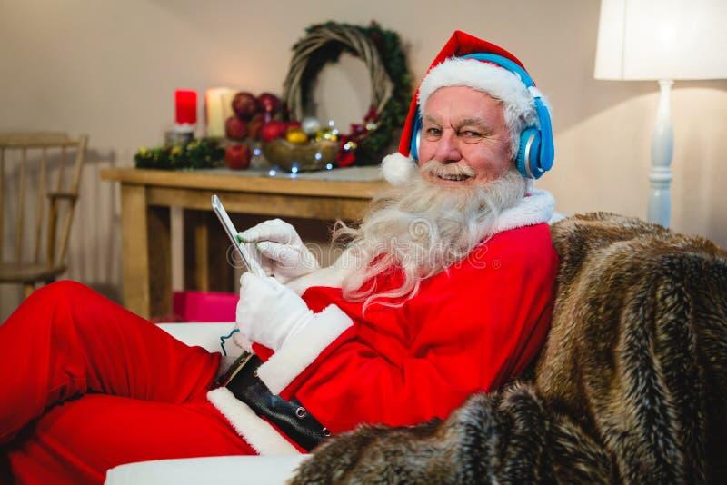 Papai Noel que usa a tabuleta digital em casa durante o tempo do Natal imagem de stock