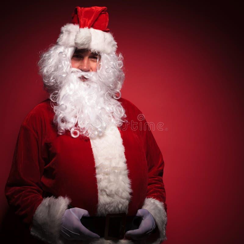 Papai Noel relaxado está estando com suas mãos na correia fotos de stock royalty free