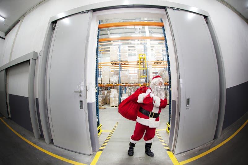 Papai Noel + saco vermelho que sae do storehouse dos presentes imagem de stock royalty free
