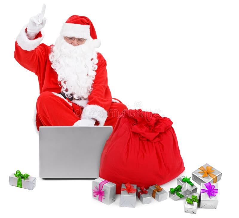 Papai Noel surpreendido com portátil e presentes imagem de stock