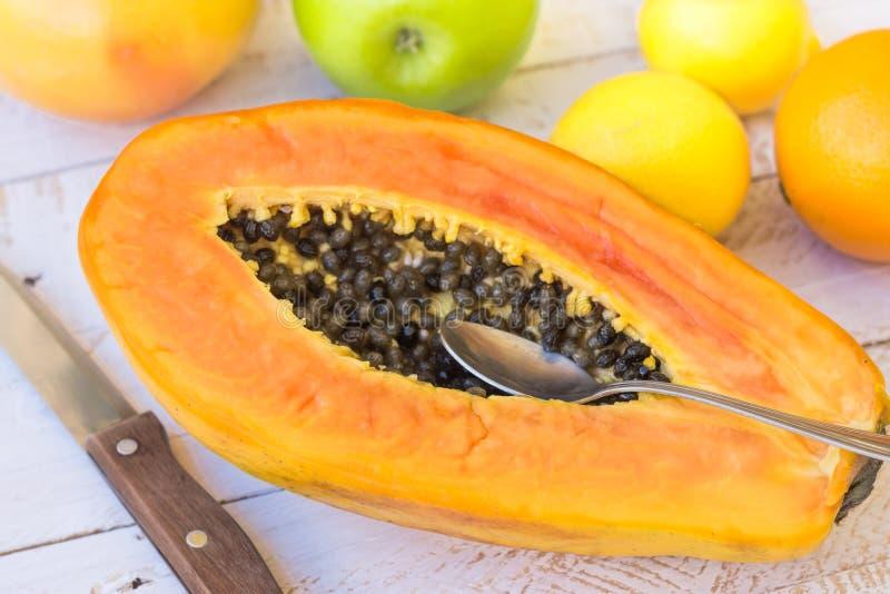 A papaia madura cortou na meia faca da colher, citrinas na tabela de madeira da prancha, luz do dia, vista superior imagem de stock