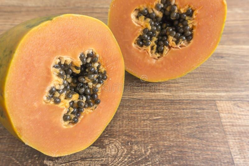 Papaia tagliata a metà nella fine su su fondo di legno immagini stock libere da diritti