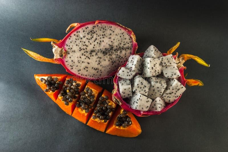 Papaja en draakfruit dat voor een dessert op zwarte achtergrond wordt gediend royalty-vrije stock afbeeldingen