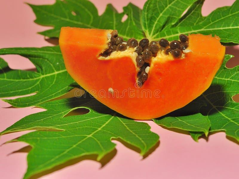 Papajafruit op roze achtergrond wordt ge?soleerd die royalty-vrije stock afbeeldingen