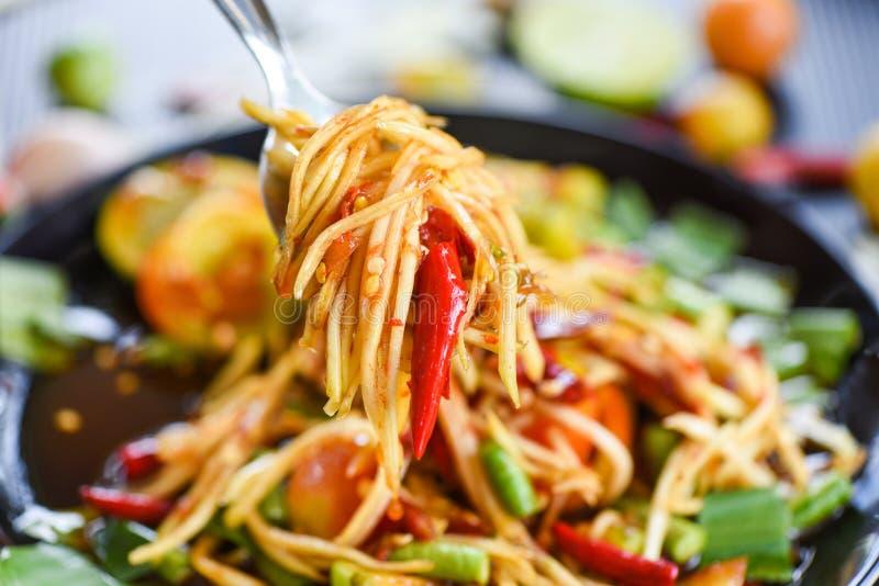 Papajasalade op een vork/Dichte omhooggaand van het groene kruidige Thaise voedsel van de papajasalade op de lijst selectieve nad stock afbeeldingen