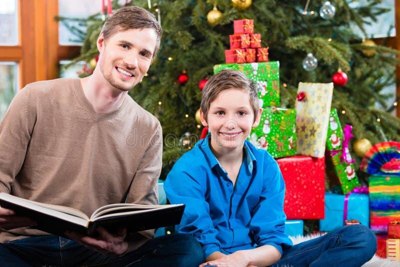 Papalezing uit van boek voor jong geitje onder Kerstmisboom stock afbeelding