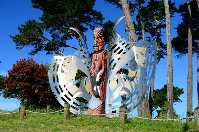 """Papamoa område, Papamoa, Nya Zeeland †""""December 22, 2018: Maoriskulptur, trä och stål, mot ljus blå himmel royaltyfri fotografi"""