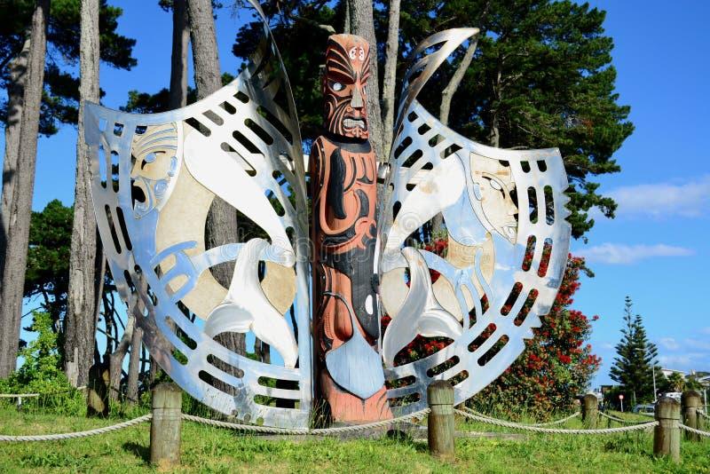 """Papamoa område, Papamoa, Nya Zeeland †""""December 22, 2018: Maoriskulptur, trä och stål, mot ljus blå himmel fotografering för bildbyråer"""