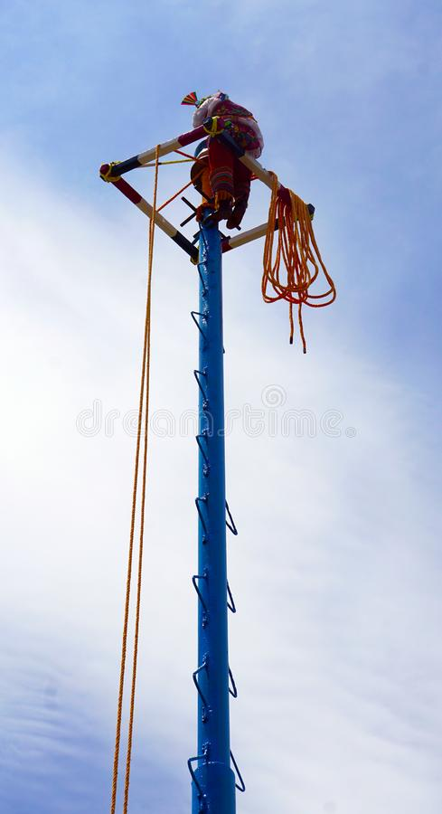 Papantla flyer boss. Famous mexican papantla flyers, main leader at the top of the post preparing the ropes to hang his partners in a touristic act in Mexican stock photography