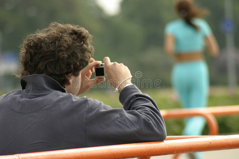 Paparazzi. A man with compact digital camera taking pictures of women stock photos