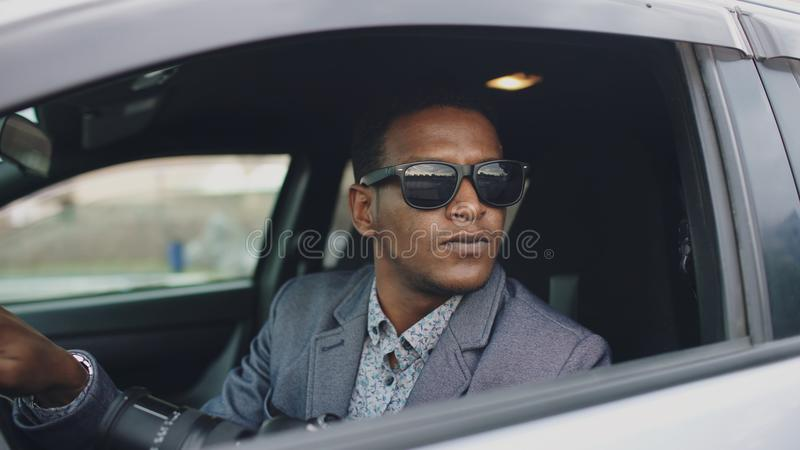 Paparazzi man sitting inside car and photographing with dslr camera royalty free stock photography