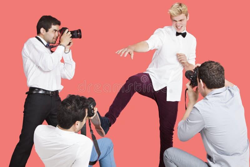 Paparazzi som tar fotografier av den manliga skådespelaren över röd bakgrund arkivbilder