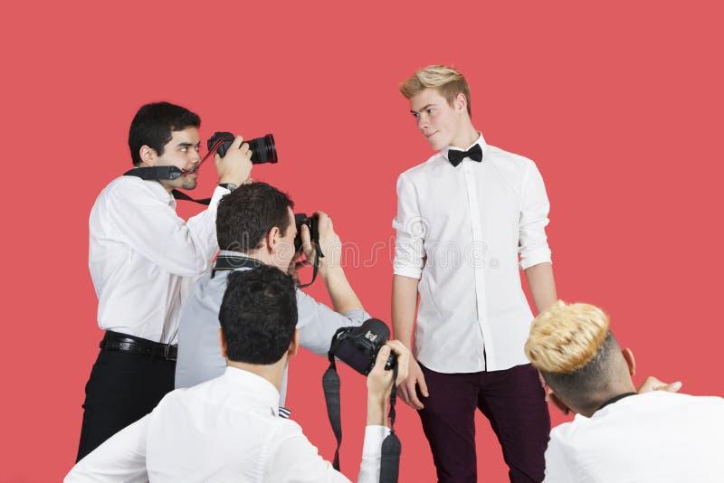 Paparazzi som tar fotografier av den manliga skådespelaren över röd bakgrund royaltyfria foton
