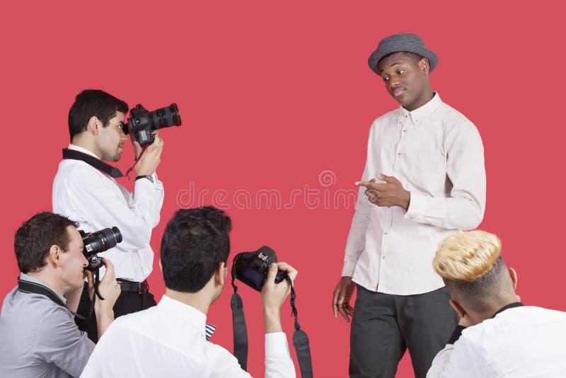 Paparazzi som tar fotografier av den manliga skådespelaren över röd bakgrund royaltyfria bilder