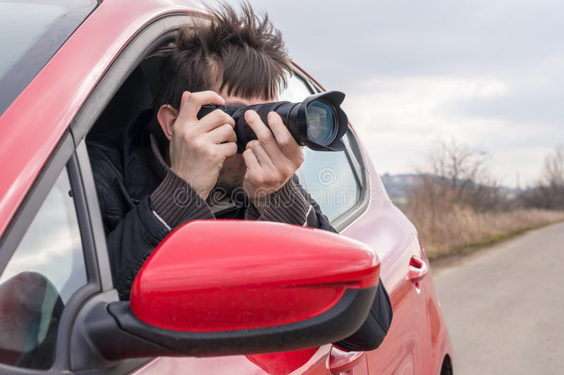 Paparazzi is taking photo with camera from car royalty free stock photo