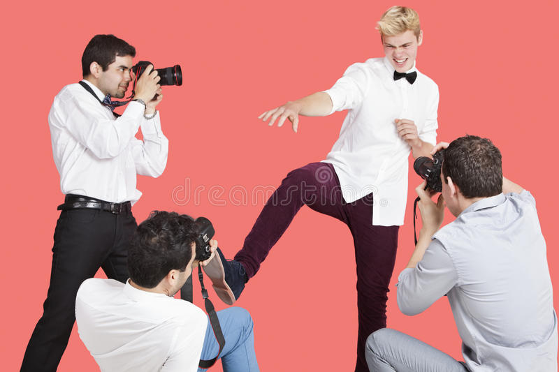 Paparazzi taking photographs of male actor over red background stock images