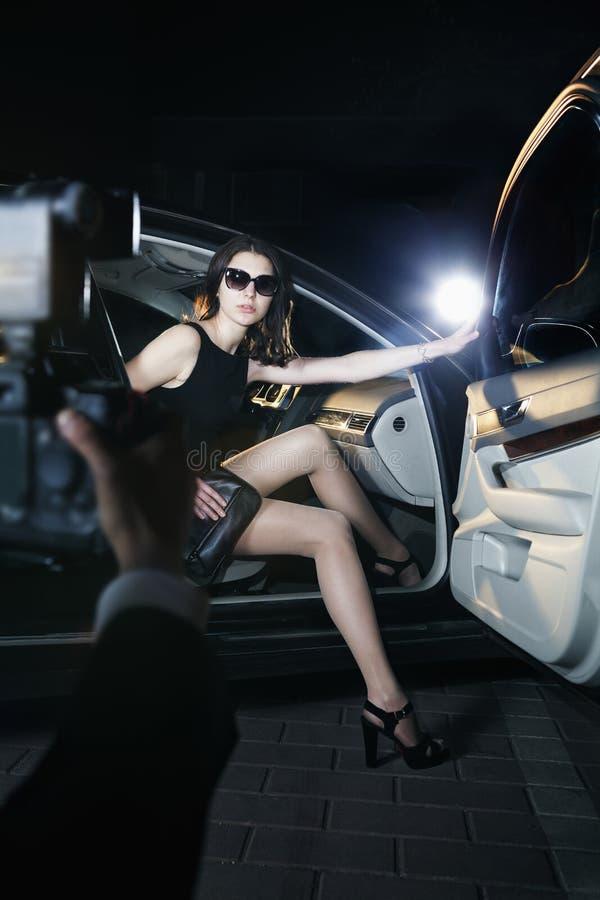 Paparazzifotograf som tar ett foto av en ung härlig kvinna som kliver ut ur en bil på en händelse för röd matta royaltyfria bilder