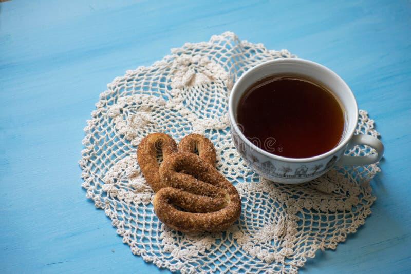 Papaver met pretzels op een blauwe raad met een kop thee Een kop thee en pretzels met kaneel stock foto