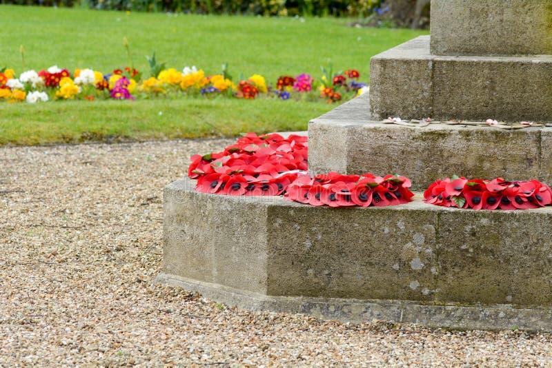 Papaverkronen bij basis van oorlogs herdenkingsstandbeeld stock foto