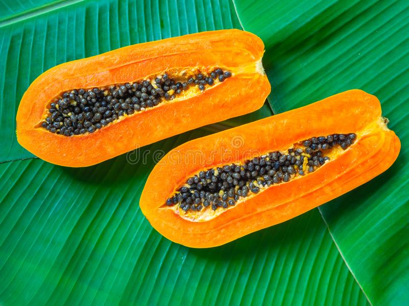 Papaya - ασιατικά τροπικά φρούτα στο πράσινο υπόβαθρο φύλλων μπανανών Μαύροι σπόροι στον πορτοκαλή πολτό στοκ φωτογραφία με δικαίωμα ελεύθερης χρήσης