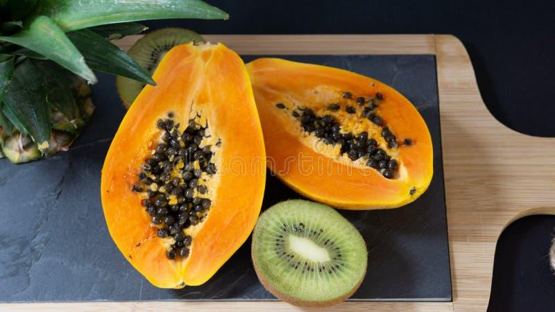 Papaya κόβεται σε δύο μισά, η στάση είναι πίνακας πετρών με ένα ξύλινο πλαίσιο στοκ εικόνες με δικαίωμα ελεύθερης χρήσης