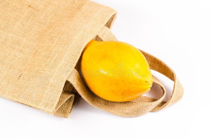 papaya amarilla fresca con el bolso del saco aislado en el fondo blanco fotografía de archivo libre de regalías