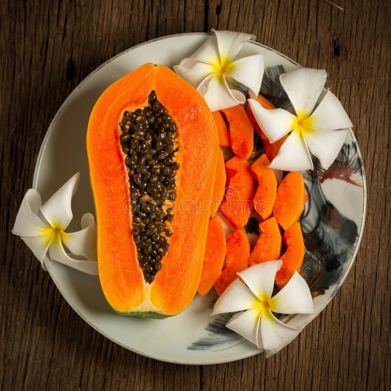 papaya fresh fruit. on dish. on old wooden. morning. sunset beau royalty free stock photos