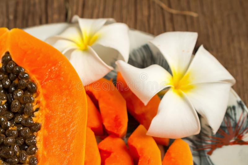 papaya fresh fruit. on dish. on old wooden. morning. sunset beau royalty free stock photo