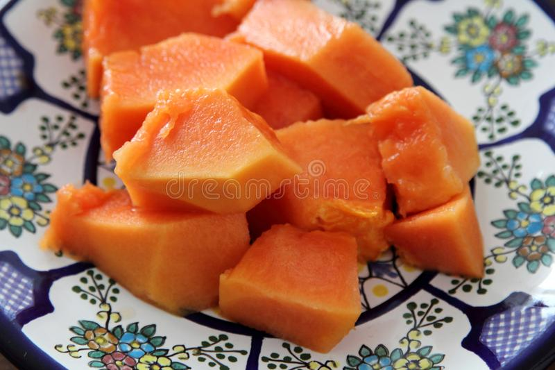 Papaya fruit or fruta bomba. Piece of ripe papaya fruit on Talavera ceramic - mexican traditional plate, ready to eat royalty free stock images