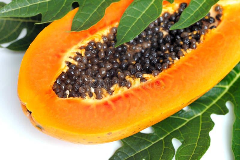 Papaya madura con las semillas y la hoja fotografía de archivo