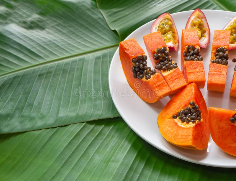 Papaya and passion fruit pieces on white plate with green banana leaves background, copy space. Exotic and tropical fruits royalty free stock photography