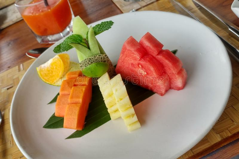 Papaya, pineapple, melon and watermelon, orange with lime and mint on a white plate on the table. Summer fruit lunch stock photography