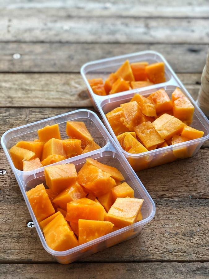 Papaya's plakken op de plastic dozen op de wijntafel met natuurlijk licht stock foto's