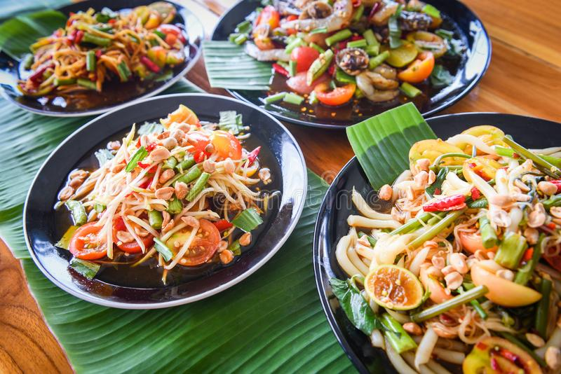 Papaya salad served on dining table / Green papaya salad spicy thai food on plate with fresh vegetables and spices seafood shrimp stock photography