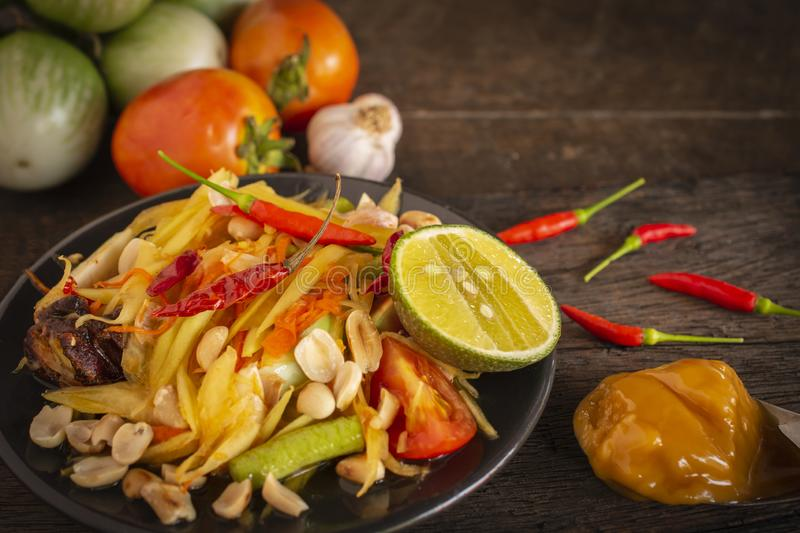 Papaya Salad Som tum Thai on black plate placed on the wood table there are garlic, eggplant, tomato, palm sugar and chilli stock photography