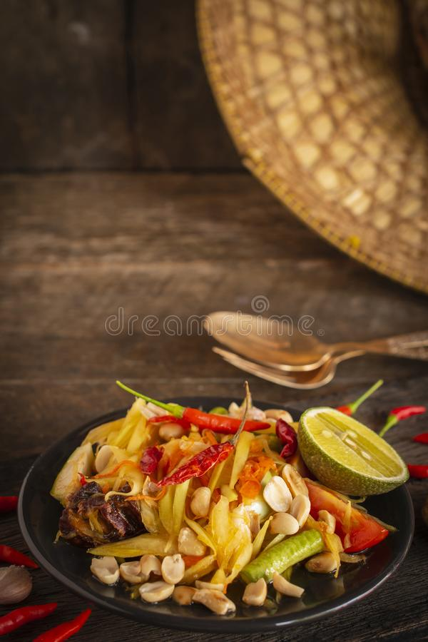 Papaya Salad Som tum Thai on black plate placed on the wood table there are garlic, fork, spoon and chilli placed around royalty free stock photos