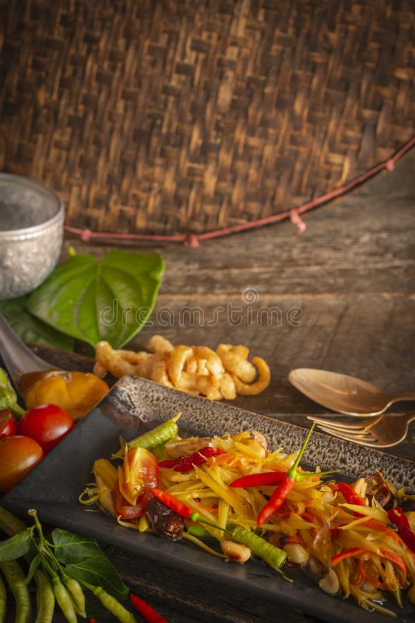 Papaya Salad Som tum Thai on square black plate placed on the wood table there are long bean, palm sugar, fork, spoon, tomato, royalty free stock images