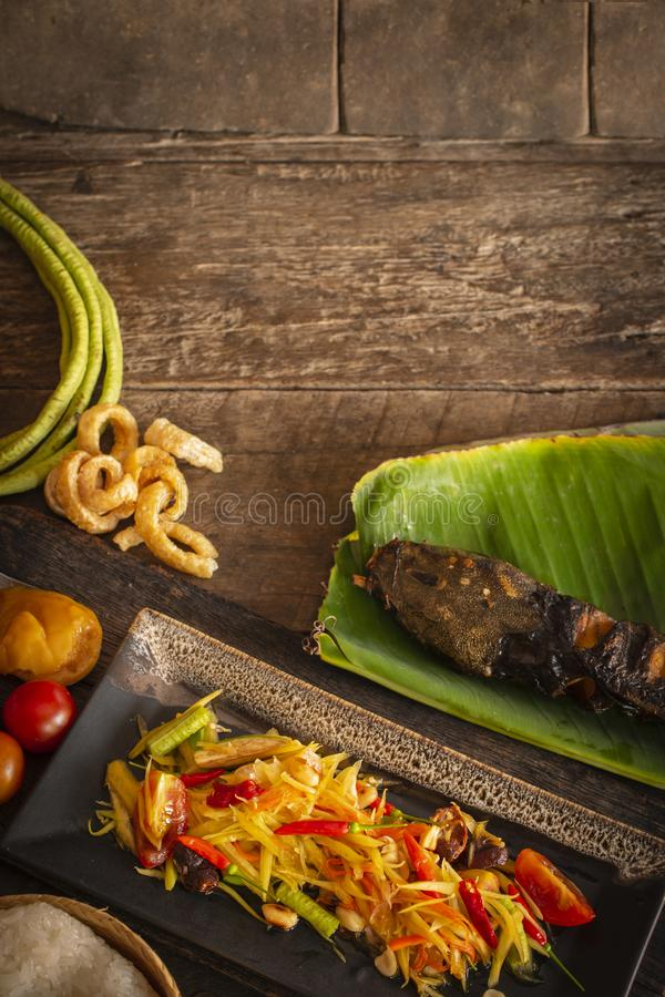 Papaya Salad Som tum Thai on square black plate placed on the wood table there are long bean, palm sugar, grilled fish, sticky royalty free stock image
