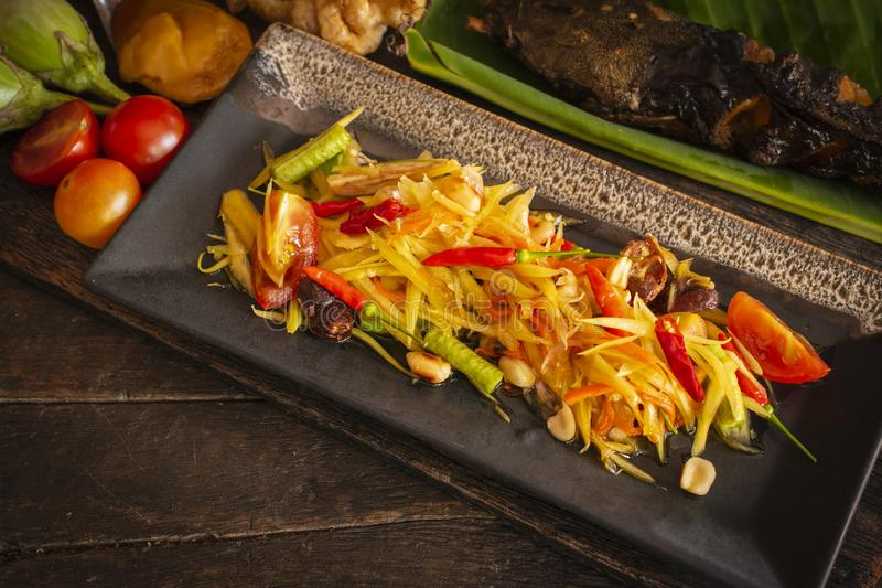 Papaya Salad Som tum Thai on square black plate placed on the wood table there are tomato, grilled fish, eggplant and palm sugar stock photos