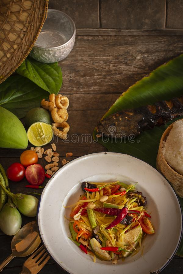 Papaya Salad Som tum Thai on white zine plate placed on the wood table there are eggplant, tomato, lemon, grilled fish, fork, royalty free stock images