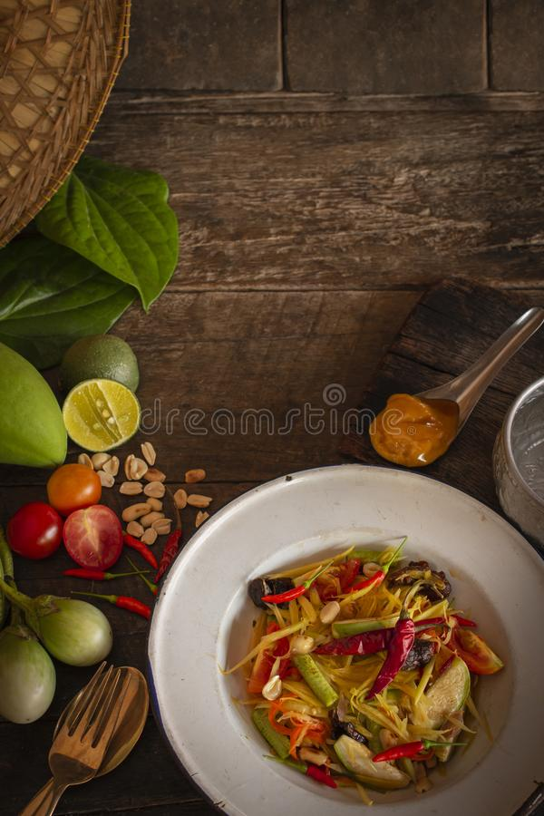 Papaya Salad Som tum Thai on white zine plate placed on the wood table there are eggplant, tomato, lemon, palm sugar, fork, stock image