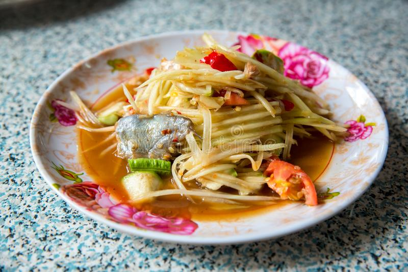Papaya salad, which put Pickled Fish and long beans. Papaya salad in white dish on wooden background. Traditional Thai style raw preserved fishthai accent is royalty free stock photos