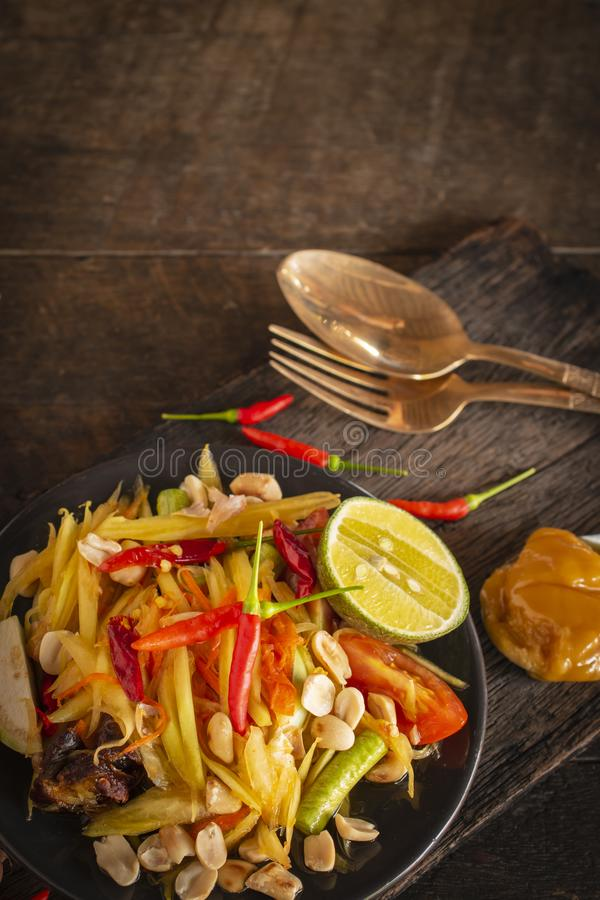 Papaya SOM tum Ταϊλανδός σαλάτας στο μαύρο πιάτο που τοποθετείται στον ξύλινο πίνακα υπάρχει ζάχαρη, δίκρανο, κουτάλι και τσίλι φ στοκ φωτογραφία