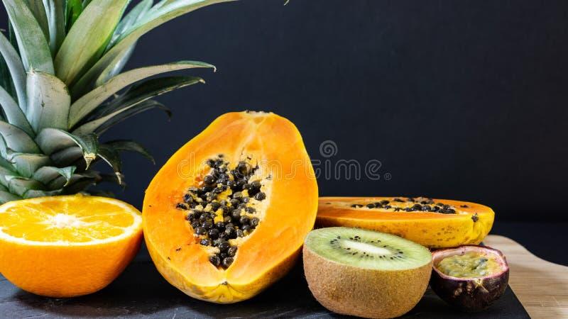 Papayaen apelsinen, kiwihalvor, stenar brädeställningen med en träram arkivbild