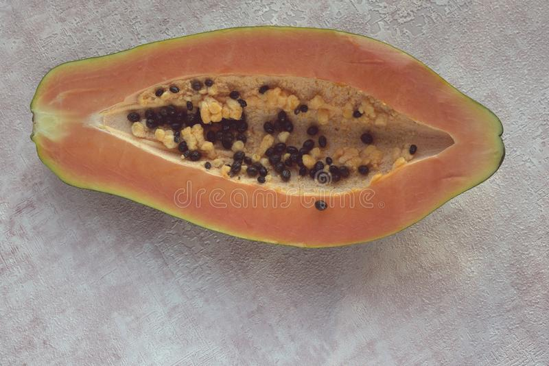 Papayaen Carica papaya ?r en exotisk, smaklig s?t frukt Frukt f?r melonbr?dtr?d mot en rosa bakgrund half Papayafr? arkivfoto
