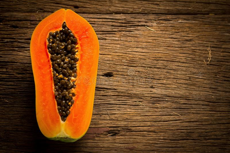 Papayafrukt half seed Gammalt trä moring Solnedgång konst asiat royaltyfri foto