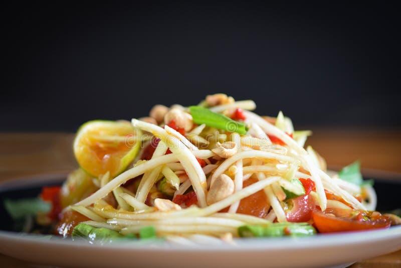 Papayasalat gedient auf Platte mit dunklem Hintergrund - schließen Sie oben vom würzigen thailändischen selektiven Fokus des grün stockbild