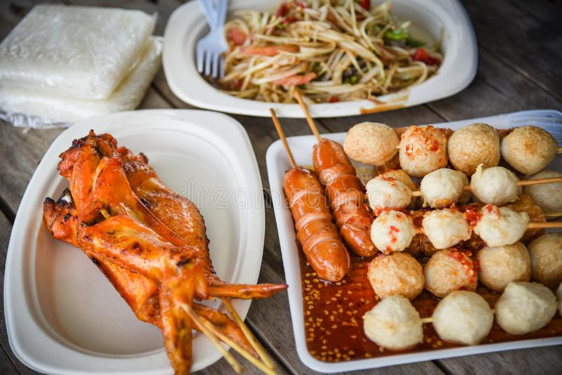 Papayasalat grillte Hühnerflügel und Fleischball mit dem klebrigen Reis, der auf thailändischer Straßennahrung der Platte gedient stockbilder