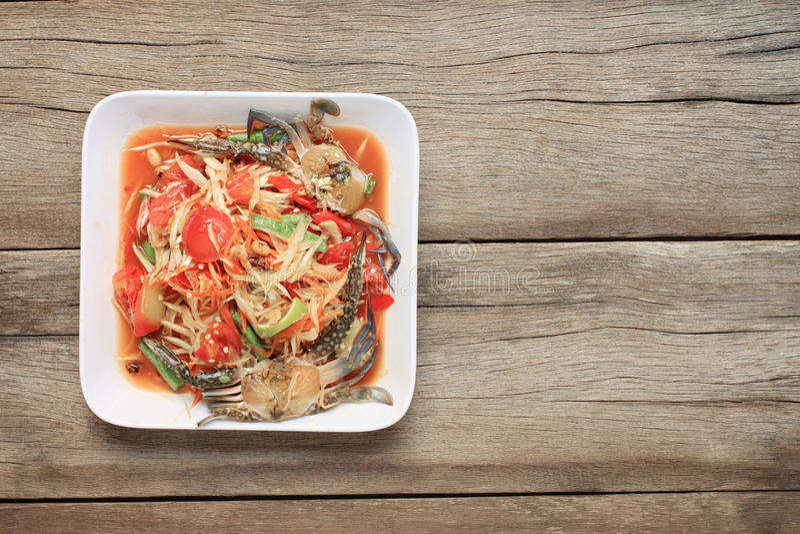 Papayasallad med krabban av thai foods i den vita maträtten på wood backg arkivbild